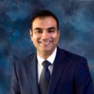 headshot of Ankit Gaur, an Indian man wearing a suit standing in front of a dar blue backdrop